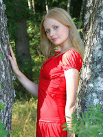 new model with silky blonde hair has shoot out in the forest among the trees.
