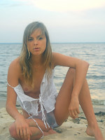 dirty blonde in see through panties on a beach all by herself.