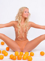 pixie sandy plays with oranges while revealing her petite breasts and fresh ass.